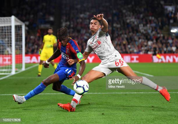 Trent AlexanderArnold of Liverpool is tackled by Wilfried Zaha of Crystal Palace during the Premier League match between Crystal Palace and Liverpool...