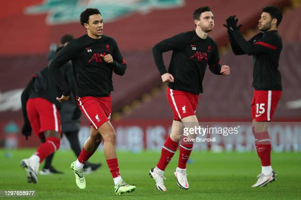 Trent Alexander-Arnold of Liverpool warms up with team mate Andy Robertson of Liverpool ahead of the Premier League match between Liverpool and...