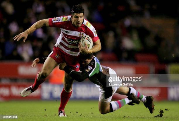 Trent Barrett of Wigan is tackled by Henry Paul of Harlequins during the engage Super League match between Wigan Warriors and Harlequins RL at the...