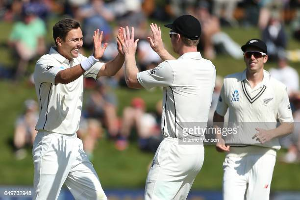 Trent Boult and Jimmy Neesham of New Zealand celebrate the dismissal of Temba Bavuma during day two of the First Test match between New Zealand and...