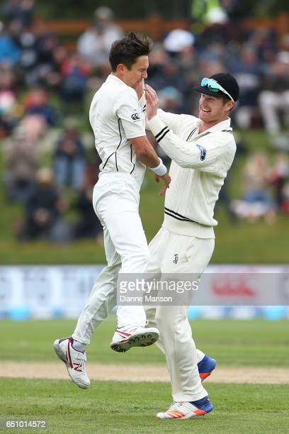 Trent Boult and Jimmy Neesham of New Zealand celebrate the dismissal of Stephen Cook of South Africa during day three of the First Test match between...