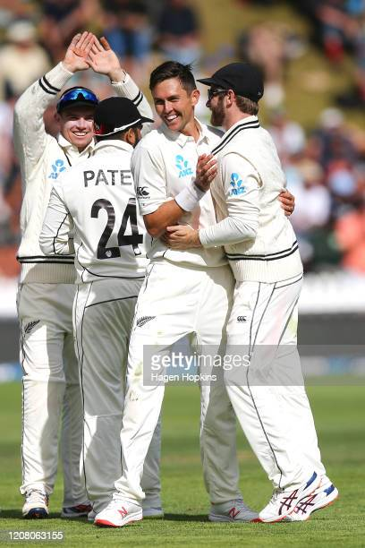 Trent Boult and Kane Williamson of New Zealand celebrate the wicket of Cheteshwar Pujara of India during day three of the First Test match between...