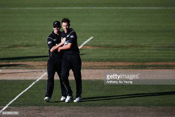 Trent Boult of New Zealand celebrate with teammate Colin Munro for the wicket of Pat Cummins of Australia during game three of the One Day...