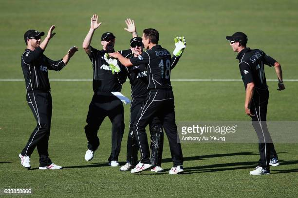 Trent Boult of New Zealand celebrates with teammates for the wicket of James Faulkner of Australia during game three of the One Day International...