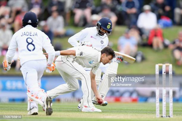 Trent Boult of New Zealand fields the ball off his own bowling during day three of the Second Test match between New Zealand and India at Hagley Oval...