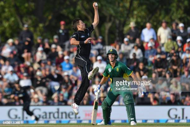 Trent Boult of New Zealand fields the ball off his own bowling during game two of the One Day International series between New Zealand and South...