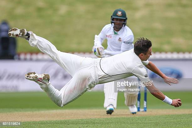 Trent Boult of New Zealand fields the ball off his own bowling while Shakib Al Hasan of Bangladesh looks on during day one of the First Test match...