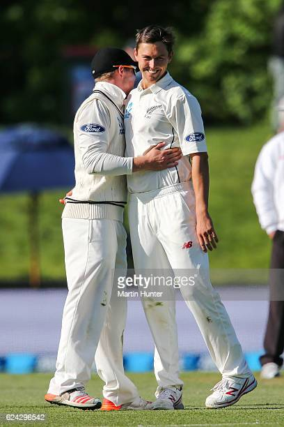 Trent Boult of New Zealand is congratulated by Henry Nicholls after bowling Sarfaraz Ahmed of Pakistan during day three of the First Test between New...