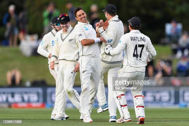 Trent Boult of New Zealand is congratulated by team mates after dismissing Cheteshwar Pujara of India during day two of the Second Test match between...