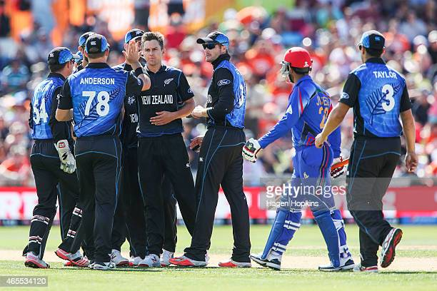 Trent Boult of New Zealand is congratulated by teammate Corey Anderson after taking the wicket of Javed Ahmadi of Afghanistan while Usman Ghani looks...