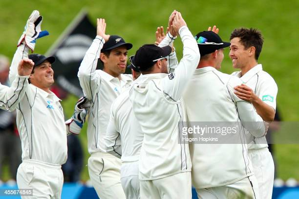 Trent Boult of New Zealand is congratulated by teammates after taking the wicket of Tino Best of the West Indies during day three of the Second Test...