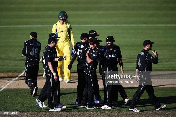 Trent Boult of New Zealand is mobbed by teammates after taking the last wicket Josh Hazlewood of Australia to win game three of the One Day...