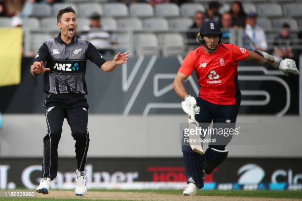 Trent Boult of New Zealand reacts with Tom Banton of England running during game five of the Twenty20 International series between New Zealand and...