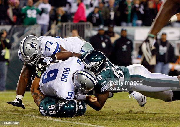 Trent Cole and Jason Babin of the Philadelphia Eagles sack quarterback Tony Romo of the Dallas Cowboys as Cowboys Tyron Smith attempts to help at...