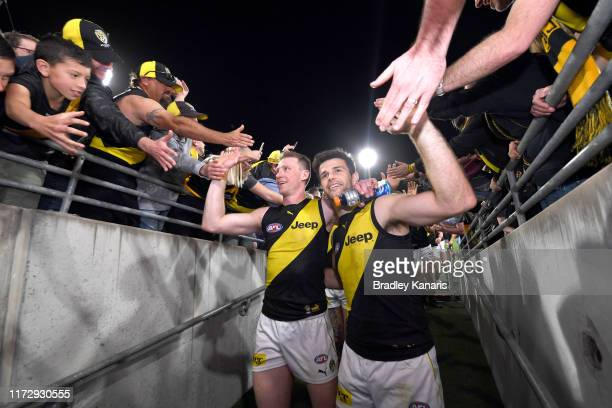 Trent Cotchin and Dylan Grimes of the Tigers celebrate victory with the fans after the AFL 2nd Qualifying Final match between the Brisbane Lions and...