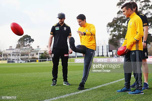 Trent Cotchin and Ivan Maric of the Tigers watch Hernanes kick a ball next to teammate Paulo Dybala of Juventus during a Richmond Tigers AFL and...