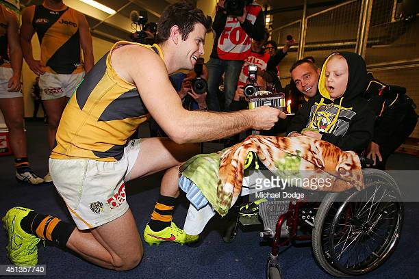 Trent Cotchin and Jake King present Tigers fan Nate Anderson suffering serious illness a birthday cake after their win during the round 15 AFL match...