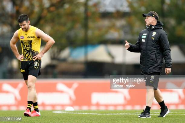 Trent Cotchin and Richmond senior coach, Damien Hardwick speak to each other while observing social distancing protocols during a Richmond Tigers AFL...