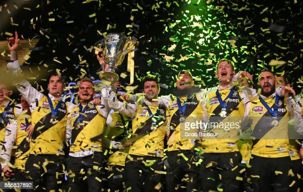 Trent Cotchin and the Tigers celebrate with the AFL Premiership Cup as confetti falls on stage during the Richmond Tigers AFL Grand Final...