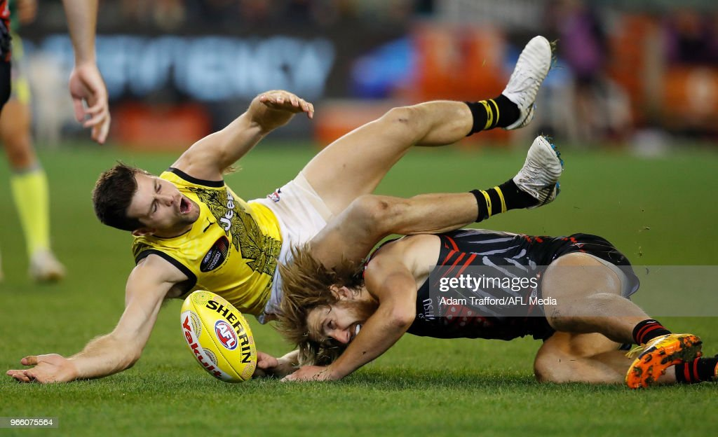 Trent Cotchin of the Tigers and Dyson Heppell of the Bombers compete for the ball during the 2018 AFL round 11 Dreamtime at the G match between the Essendon Bombers and the Richmond Tigers at the Melbourne Cricket Ground on June 02, 2018 in Melbourne, Australia.