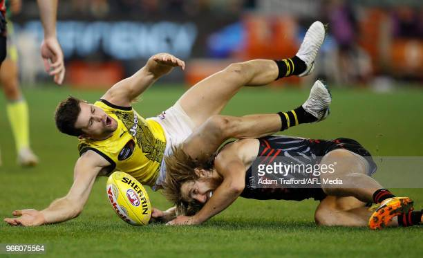 Trent Cotchin of the Tigers and Dyson Heppell of the Bombers compete for the ball during the 2018 AFL round 11 Dreamtime at the G match between the...
