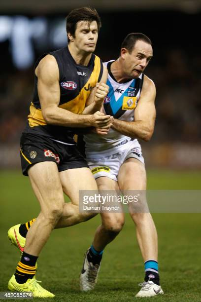 Trent Cotchin of the Tigers and Matthew Broadbent of the Power collide during the round 17 AFL match between the Richmond Tigers and the Port...