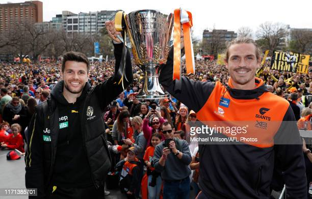 Trent Cotchin of the Tigers and Phil Davis of the Giants pose with the premiership cup during the Toyota AFL Grand Final Parade on September 27, 2019...