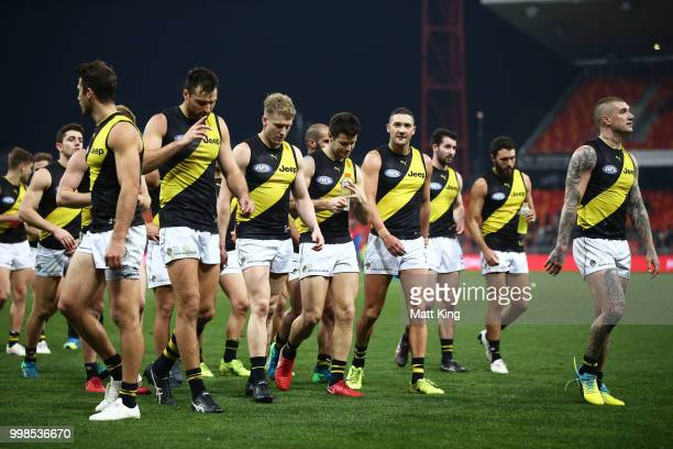 Trent Cotchin of the Tigers and team mates look dejected as they leave the pitch during the round 17 AFL match between the Greater Western Sydney...