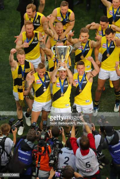 Trent Cotchin of the Tigers Dustin Martin of the Tigers celebrate with the the AFL Premiership Cup and supporters in the crowd as the Tigers make...