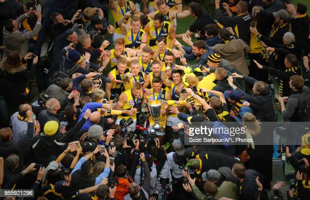 Trent Cotchin of the Tigers, Dustin Martin of the Tigers celebrate with the the AFL Premiership Cup and supporters in the crowd as the Tigers make...