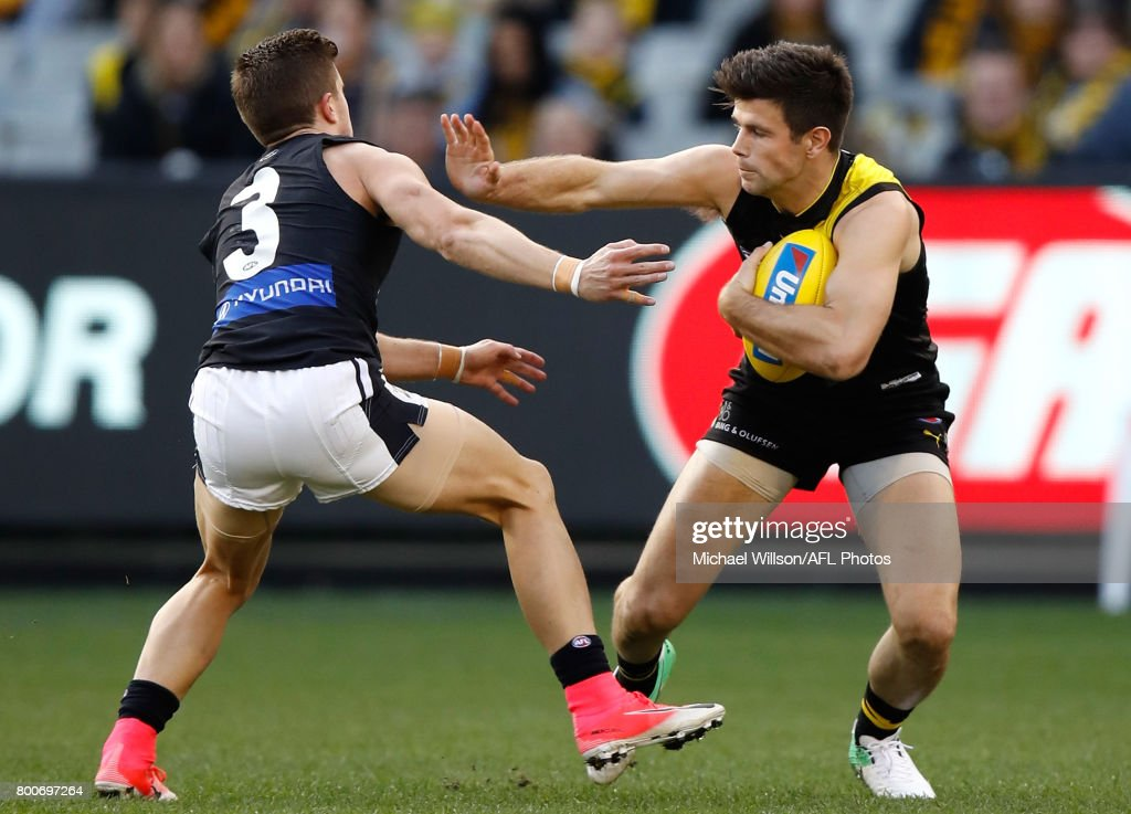 Trent Cotchin of the Tigers fends off Marc Murphy of the Blues during the 2017 AFL round 14 match between the Richmond Tigers and the Carlton Blues at the Melbourne Cricket Ground on June 25, 2017 in Melbourne, Australia.