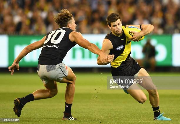 Trent Cotchin of the Tigers gets around a tackle by Charlie Curnow of the Blues during the round one AFL match between the Richmond Tigers and the...