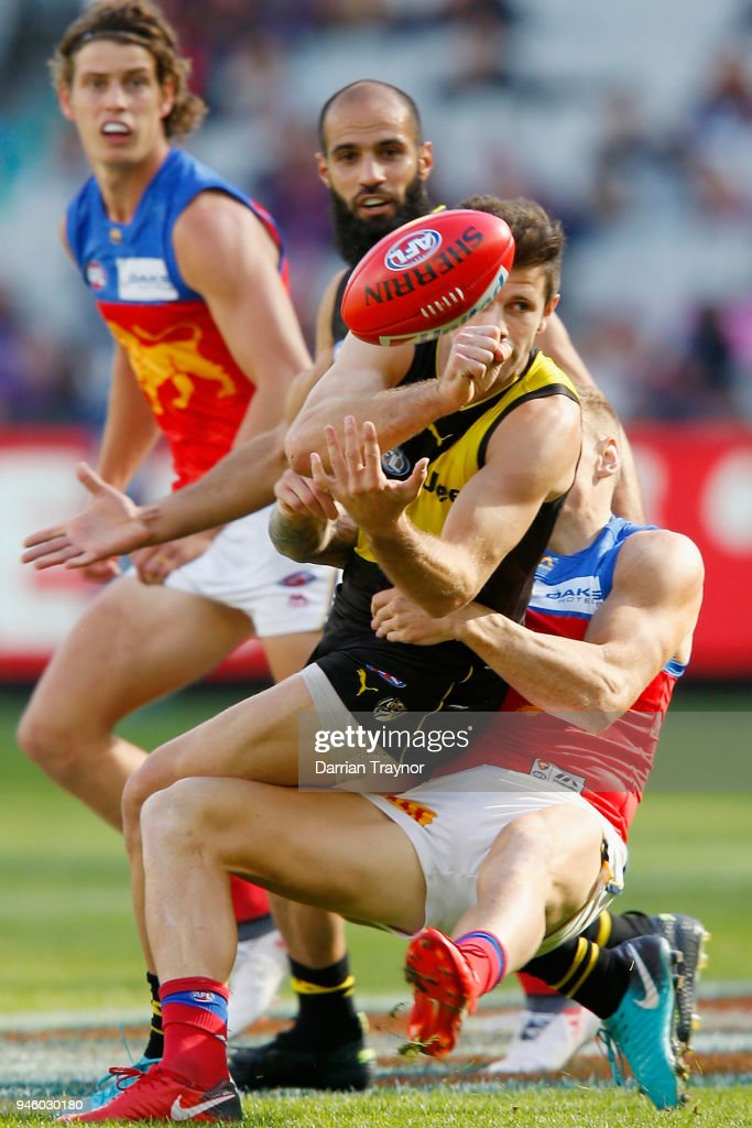 Trent Cotchin of the Tigers handballs during the round four AFL match between the Richmond Tigers and the Brisbane Lions at Melbourne Cricket Ground on April 14, 2018 in Melbourne, Australia.