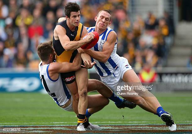 Trent Cotchin of the Tigers handballs whilst being tackled by Luke McDonald and Drew Petrie of the Kangaroos during the round six AFL match between...