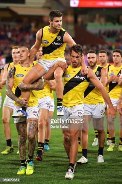Trent Cotchin of the Tigers is chaired off the field by Dustin Martin of the Tigers and Alex Rance of the Tigers during the round two AFL match...