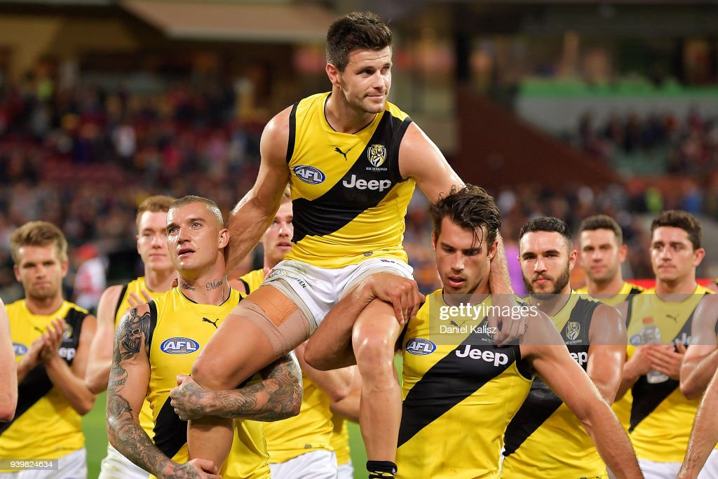 Trent Cotchin of the Tigers is chaired off the field by Dustin Martin of the Tigers and Alex Rance of the Tigers during the round two AFL match between the Adelaide Crows and the Richmond Tigers at Adelaide Oval on March 29, 2018 in Adelaide, Australia.