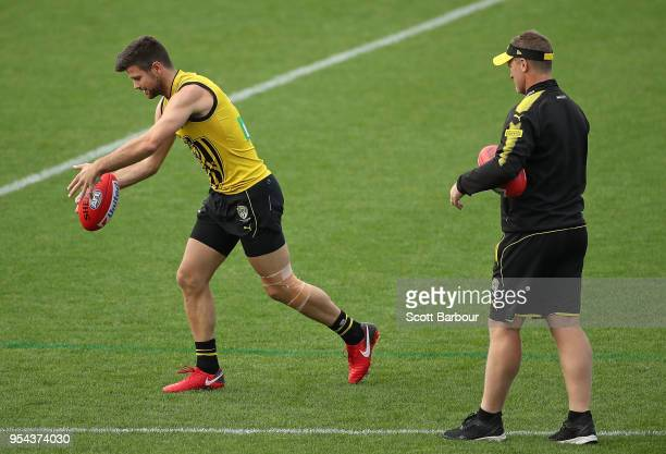 Trent Cotchin of the Tigers kicks the ball with a taped knee as Damien Hardwick coach of the Tigers looks on during the Richmond Tigers AFL training...