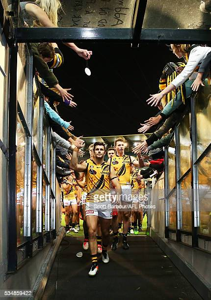Trent Cotchin of the Tigers leads his side from the field after winning the round 10 AFL match between the Essendon Bombers and the Richmond Tigers...