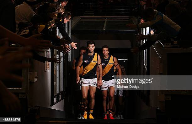 Trent Cotchin of the Tigers leads the team out next to Brett Deledio of the Tigers during the round one AFL match between the Carlton Blues and the...