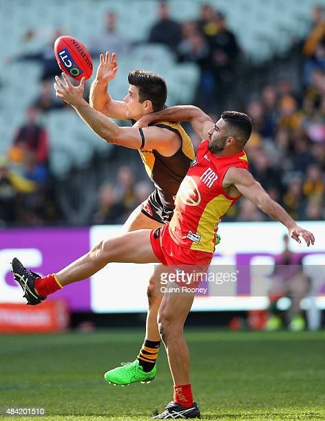 Trent Cotchin of the Tigers marks infront of Adam Saad of the Suns during the round 20 AFL match between the Richmond Tigers and the Gold Coast Suns...