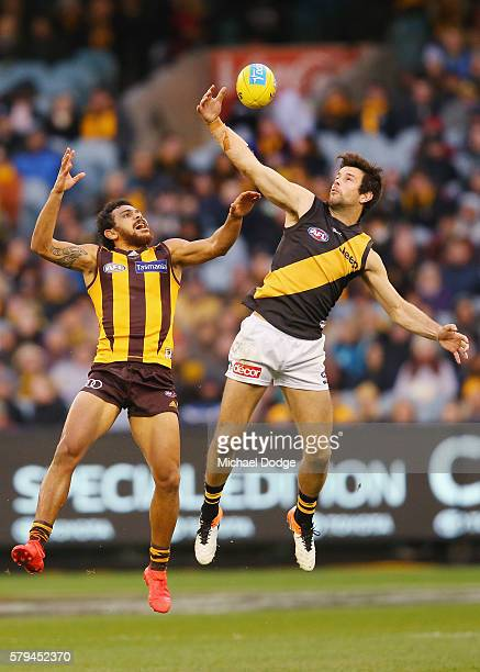 Trent Cotchin of the Tigers marks the ball one handed against Cyril Rioli of the Hawks during the round 18 AFL match between the Hawthorn Hawks and...