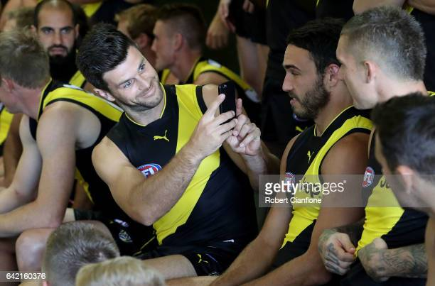 Trent Cotchin of the Tigers takes a photo of his team mates on his phone during the Richmond Tigers AFL Team Photo Day on February 17 2017 at Punt...