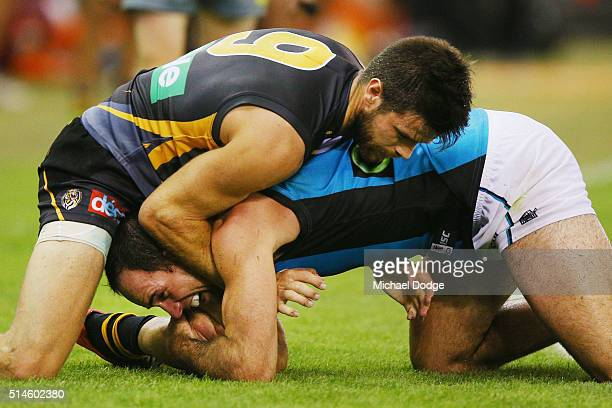 Trent Cotchin of the Tigers wrestles with Matthew Broadbent of the Power during the 2016 AFL NAB Challenge match between the Richmond Tigers and the...