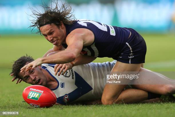 Trent Dumont of the Kangaroos and Ed Langdon of the Dockers contest for the ball during the round 10 AFL match between the Fremantle Dockers and the...