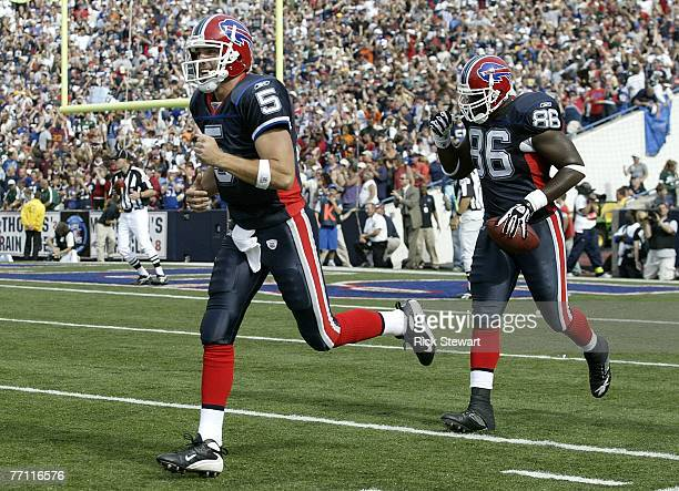 Trent Edwards of the Buffalo Bills runs off the field with Michael Gaines after Edwards threw his first NFL touchdown pass to Gaines against the New...