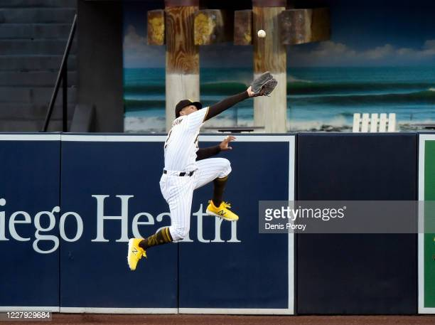 Trent Grisham of the San Diego Padres can't make a leaping catch on a triple hit by Chris Taylor of the Los Angeles Dodgers during the second inning...