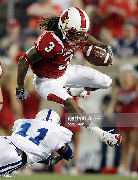 Trent Guy of the Louisville Cardinals jumps over Mike Woods of the Indiana State Sycamores during the game at Papa John's Cardinal Stadium on...