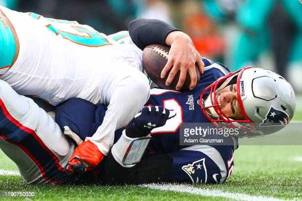 Trent Harris of the Miami Dolphins sacks Tom Brady of the New England Patriots during a game at Gillette Stadium on December 29, 2019 in Foxborough,...