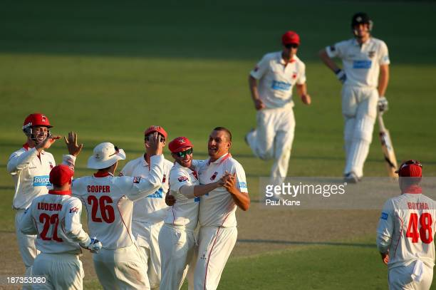Trent Lawford of the Redbacks celebrates with Phil Hughes the wicket of Jason Behrendorff of the Warriors during day three of the Sheffield Shield...