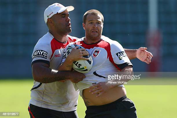 Trent Merrin is tackled by Josh Ailaomai during a St George Illawarra Dragons NRL training session at WIN Stadium on April 2 2014 in Wollongong...
